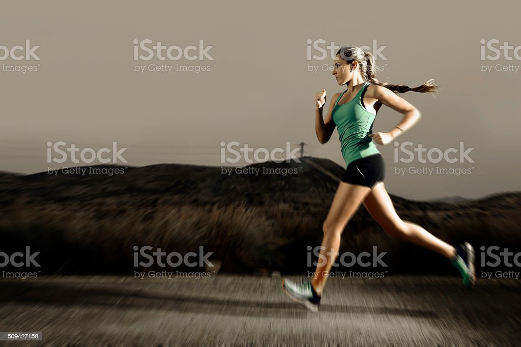 young fit sport woman running outdoors on asphalt road stock photo