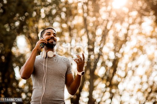 istock Young fit sportsman talking on a mobile phone in a public park 1144867265