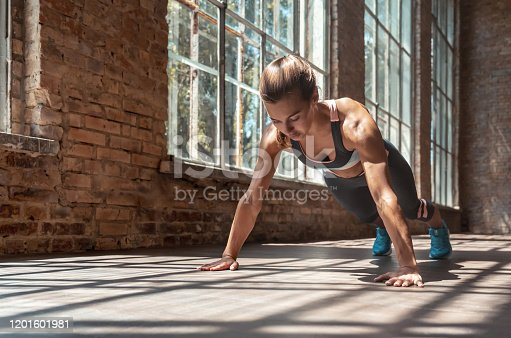 Young fit sporty active woman wear sportswear standing in plank pose doing yoga fitness training workout stretching core push up exercise on wooden floor in modern sunny gym space indoors, pushups