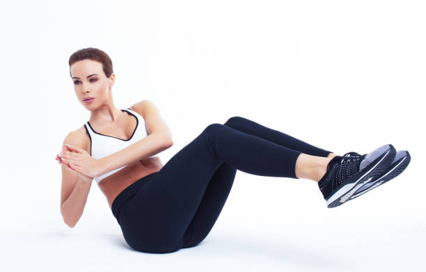 young fit woman doing russian twist exercise - twisted stock pictures, royalty-free photos & images