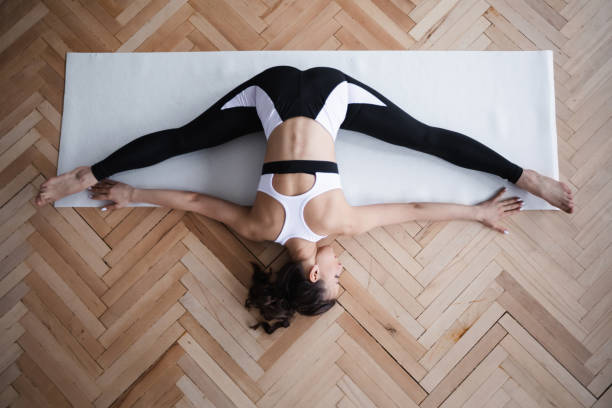 Young fit woman doing stretching top view. stock photo