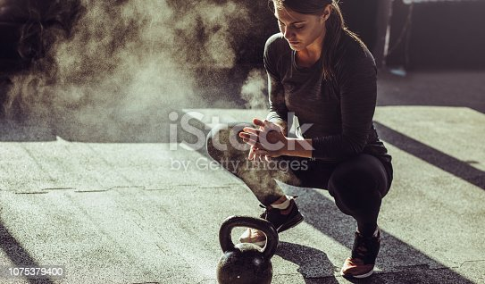 Young fit woman exercise with kettleball at gym