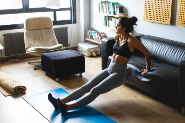 Young fit woman exercising at home Fitness workout at home. Healthy fit young woman doing triceps dips exercise in the living room. bicep stock pictures, royalty-free photos & images