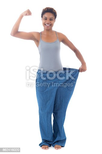 istock Young fit woman flexes muscles wearing bigger sized jeans 862416020