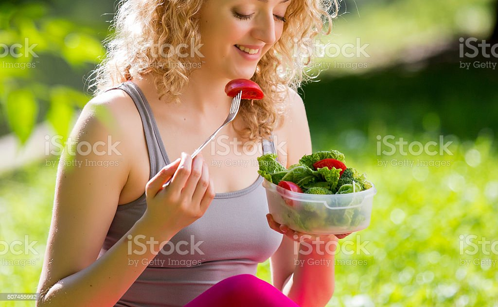 Young fit woman having snack in park stock photo
