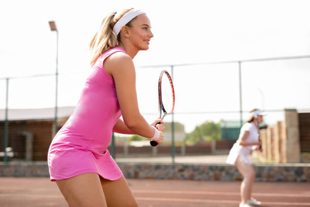 Young fit woman in pink sports dress with racket stock photo