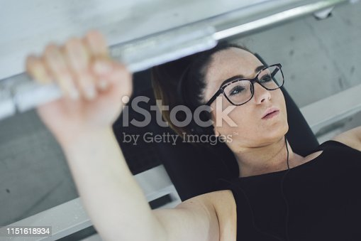 670937518istockphoto Young fit woman in sportswear exercising with weights at gym 1151618934