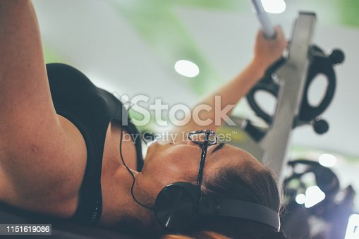 670937518istockphoto Young fit woman in sportswear exercising with weights at gym 1151619086