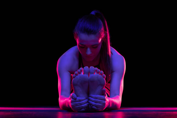 Young fit woman practicing yoga. Neon light. Modern sci fi representation of yoga. Tranquil atmosphere. Copy space. stock photo