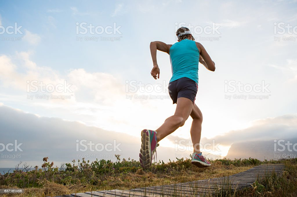 Young fit woman running on a trail stock photo