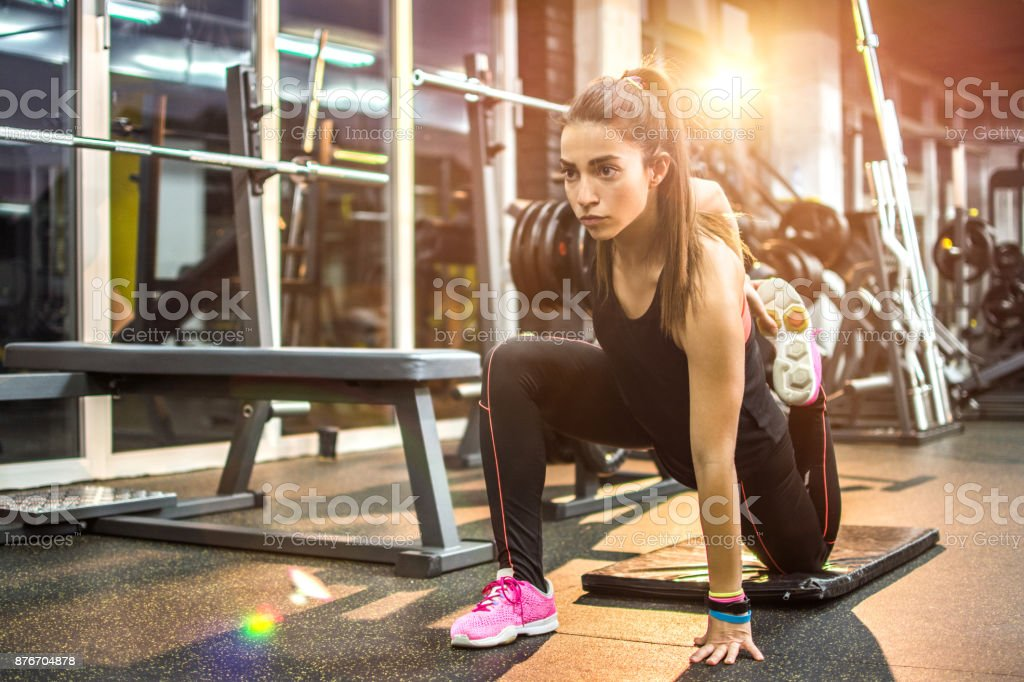 Young fit woman stretching on exercise mat in gym. stock photo