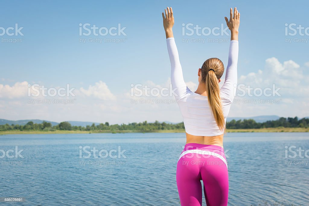 Young fit woman with hands raised at the beach stock photo