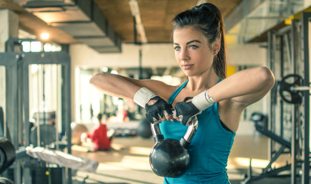 young fit woman working out with a kettle bell in the gym. - sports glove stock photos and pictures