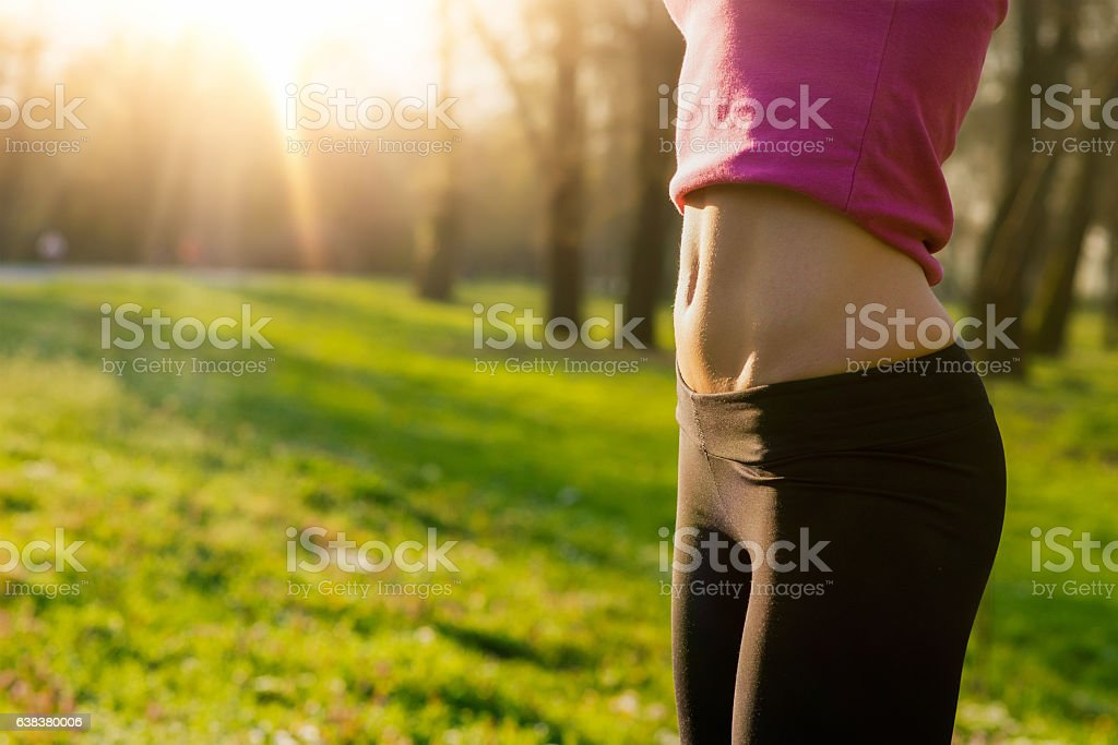 Young fit woman's belly outdoors in summer stock photo
