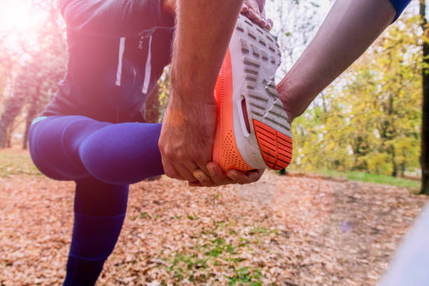 Young fitness couple stretching their muscles before running. stock photo