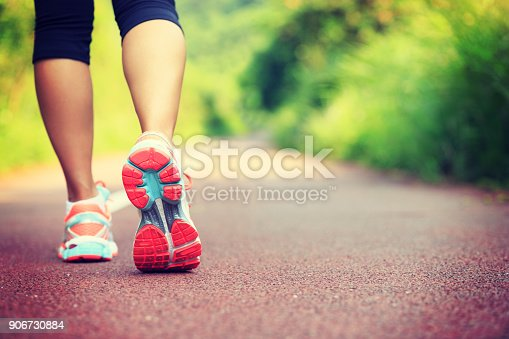 istock Young fitness female runner legs ready for run on forest trail 906730884