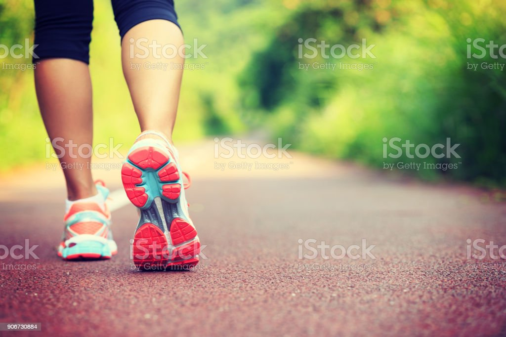 Young fitness female runner legs ready for run on forest trail stock photo
