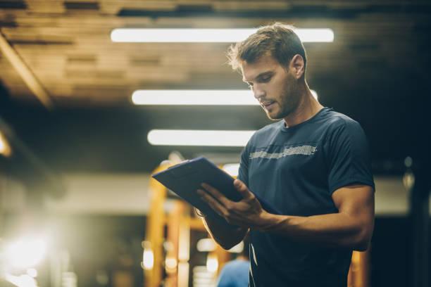 Instructeur de fitness jeune lecture un plan de formation dans une salle de gym. - Photo