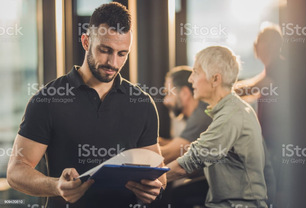 Young fitness instructor reading training plan in a health club. stock photo