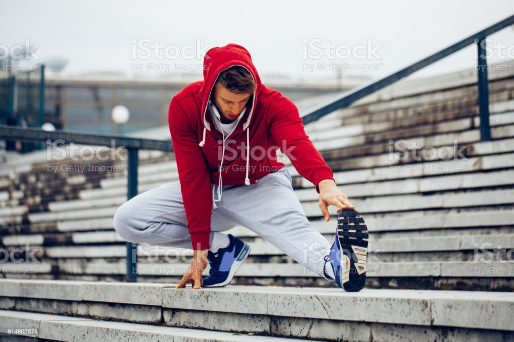 Young fitness man runner stretching legs before running on the stairs stock photo
