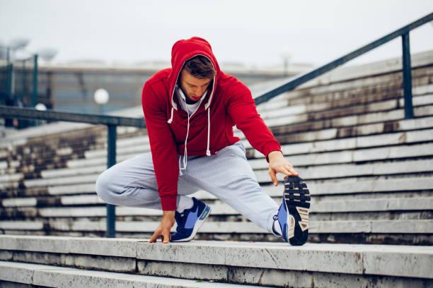 Junge Fitness Mann Läufer dehnen Beine vor der Ausführung auf der Treppe – Foto