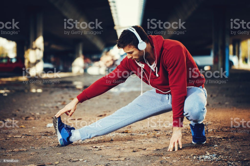 Young fitness man runner stretching legs before running photo libre de droits