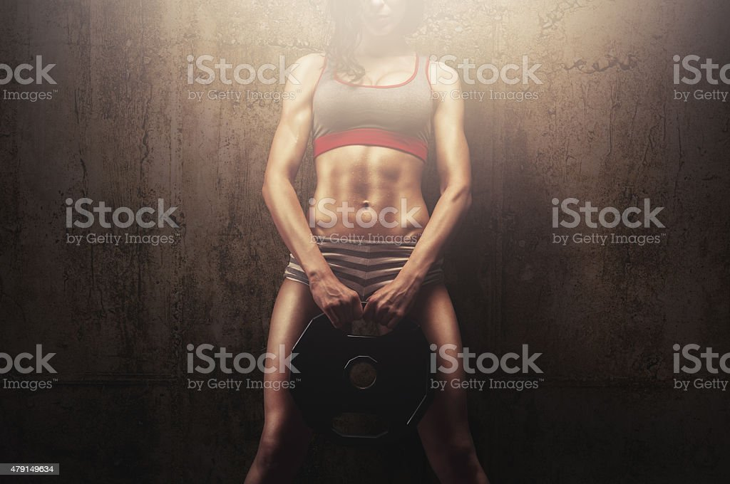 Young fitness model athlete holding weight plate stock photo