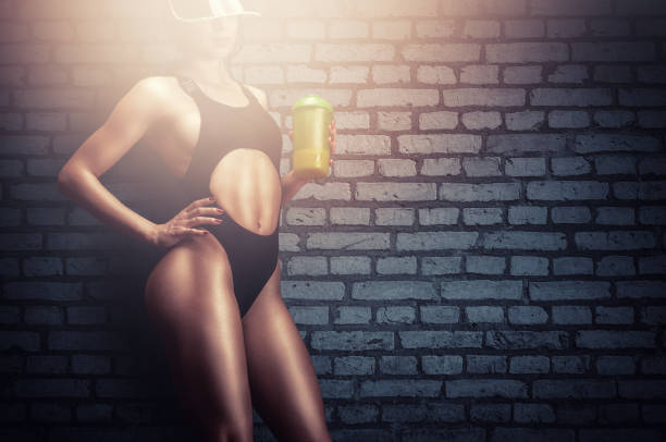Young fitness model drinking protein shake in gym stock photo