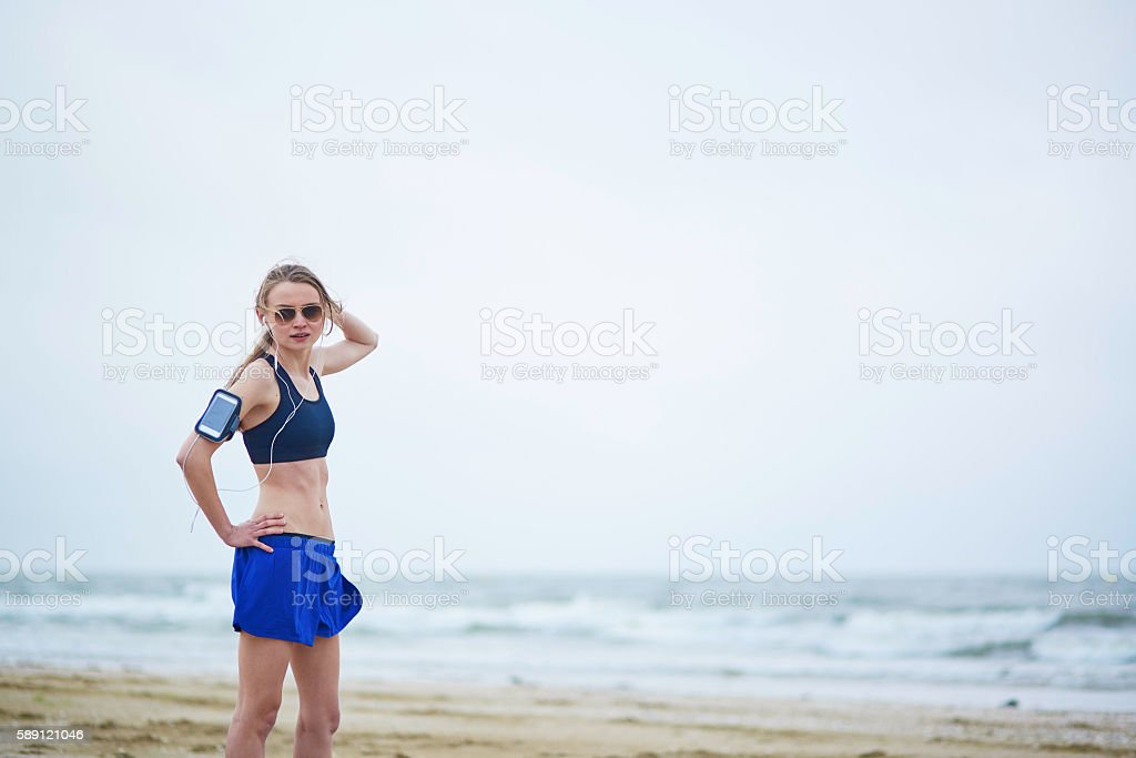 Young fitness running woman jogging on beach stock photo