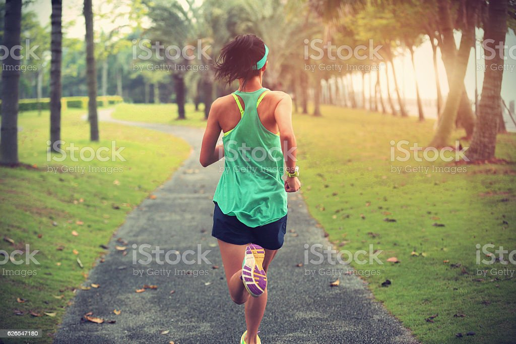 young fitness sports woman runner running on tropical park trail stock photo