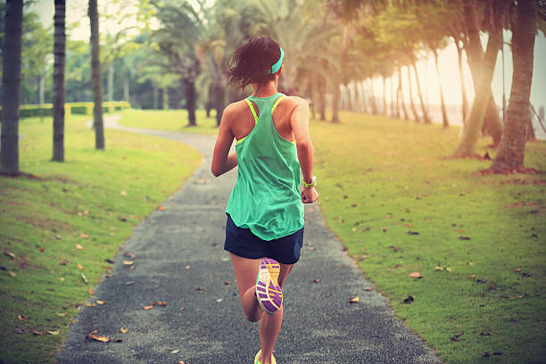 young fitness sports woman runner running on tropical park trail 스톡 사진
