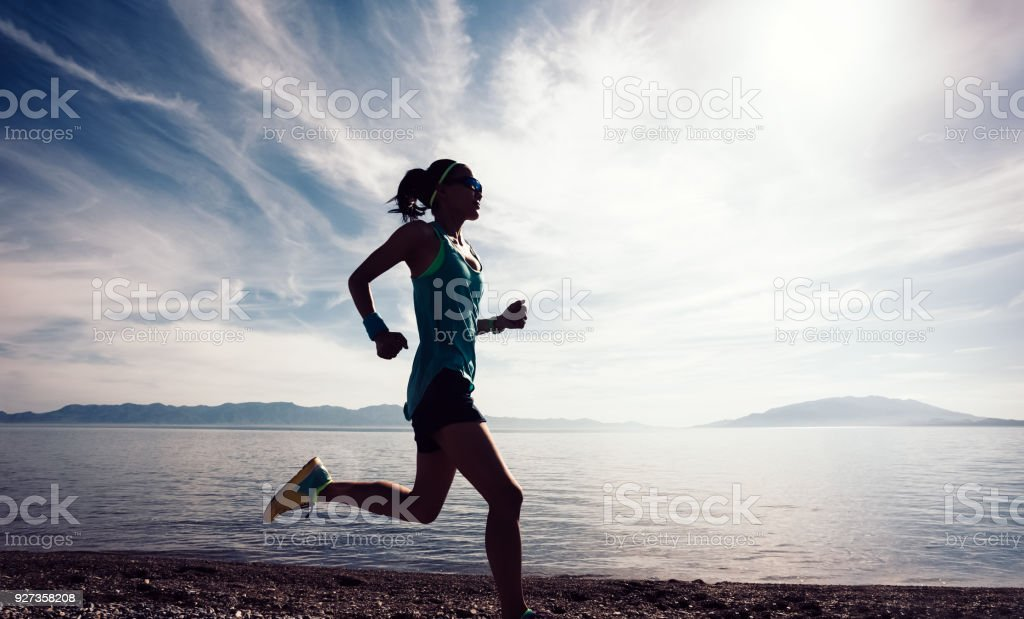Young fitness sporty woman running on rocky seaside – zdjęcie