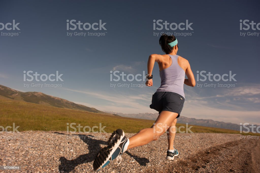 Young fitness sporty woman running on rocky seaside - Royalty-free Activity Stock Photo