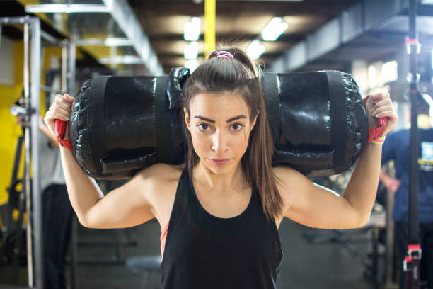 Young fitness woman carrying on fitness bag on her shoulders at gym. stock photo