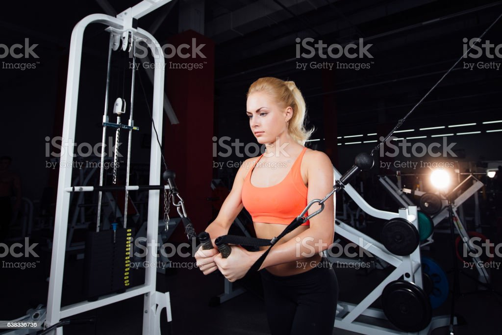 young fitness woman demonstrate crossover exercises. The pectoral muscles, hard stock photo