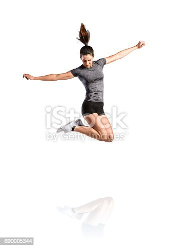istock Young fitness woman jumping high. Studio shot, isolated. 690005344