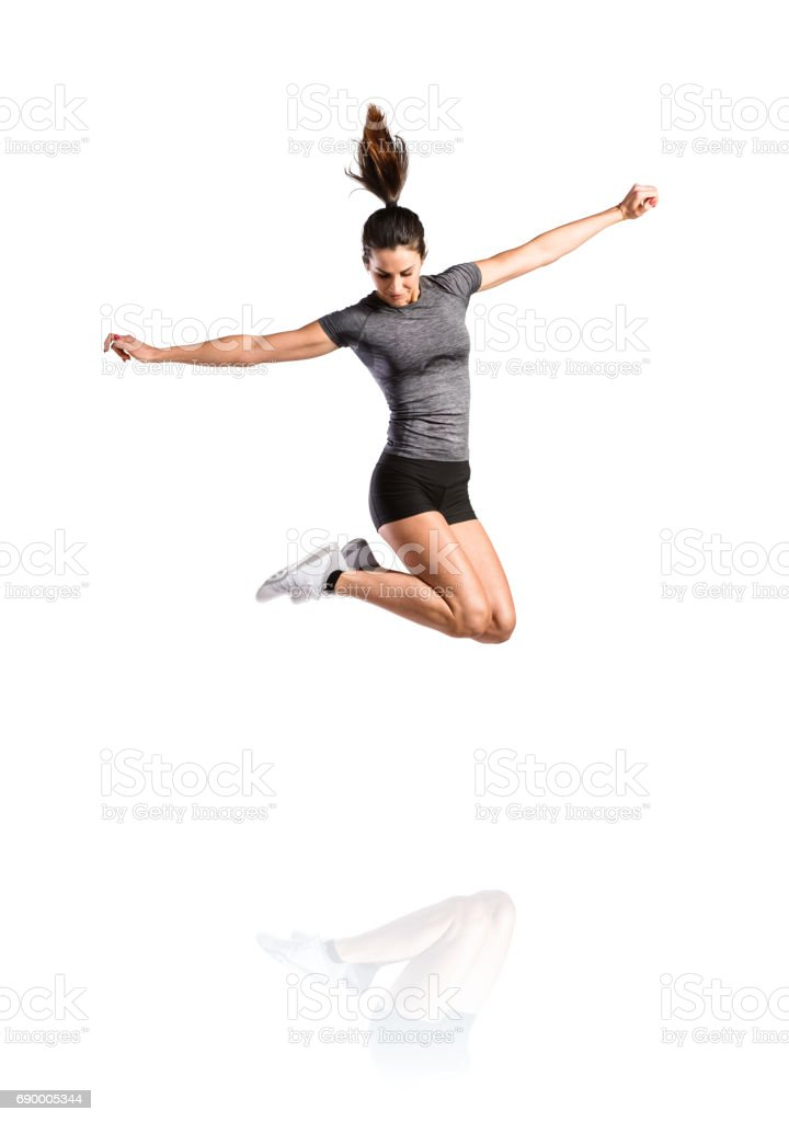 Young fitness woman jumping high. Studio shot, isolated. - foto stock