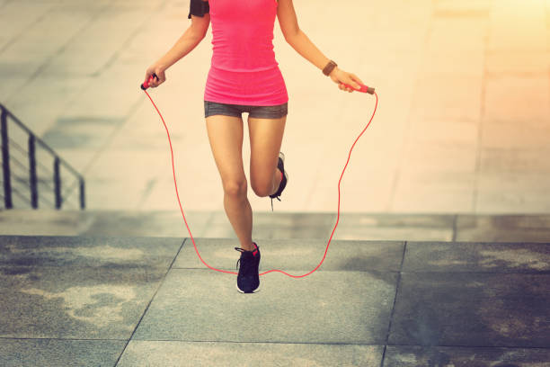 young fitness woman jumping rope on city stock photo