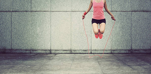 young fitness woman jumping rope outdoor - leinenhosen frauen stock-fotos und bilder