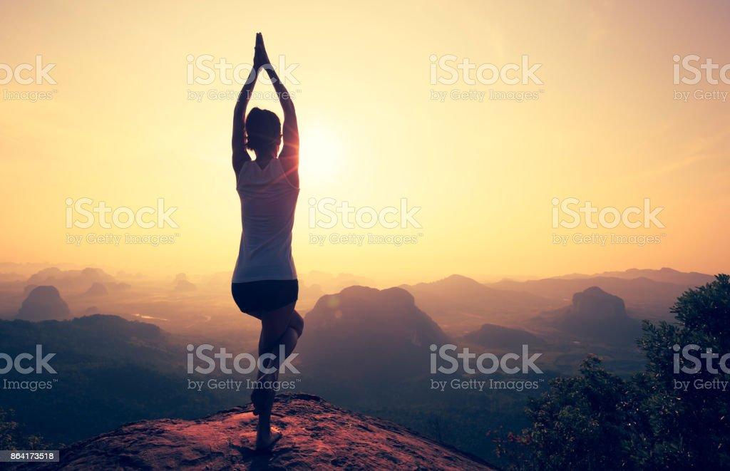 young fitness woman meditating on sunrise mountain peak royalty-free stock photo