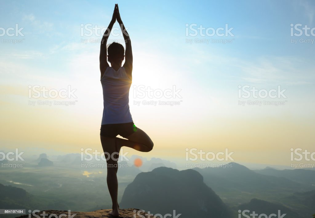 young fitness woman meditating on sunrise mountain peak royalty-free stock photo