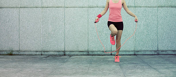 young fitness woman rope skipping against city wall stock photo