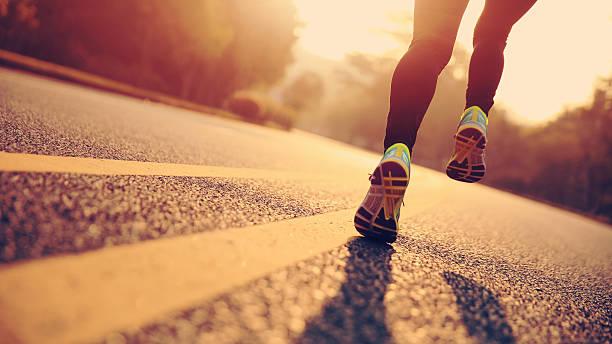 jóvenes gimnasio mujer de corredor en carretera corriendo atleta las piernas - foto de stock