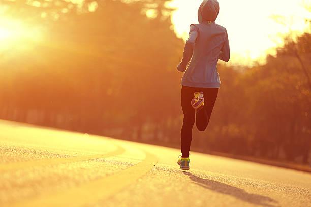 junge eignung frau läufer athlet läuft in sonnenaufgang straße - straßentraining stock-fotos und bilder