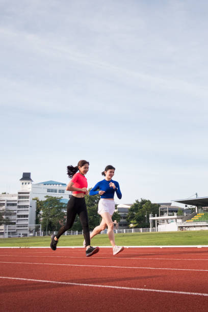 Young fitness woman runner jogging excercise in the morning on city stadium track in the city. Female athlete excercise in the city stadium to keep body fitness stock photo