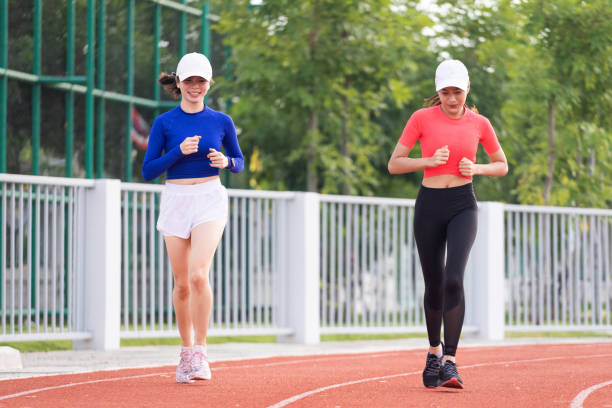 Young fitness woman runner jogging excercise in the morning on stadium track in the city. Female athlete excercise in the city stadium to keep body fitness during COVID-19 pandemic. stock photo