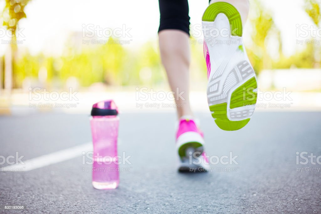 Young fitness woman runner legs running stock photo