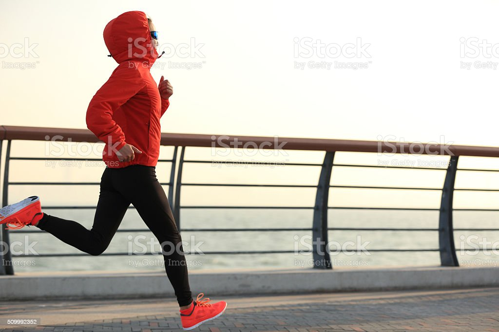 young fitness woman runner running at sunrise seaside young fitness woman runner running at sunrise seaside Active Lifestyle Stock Photo