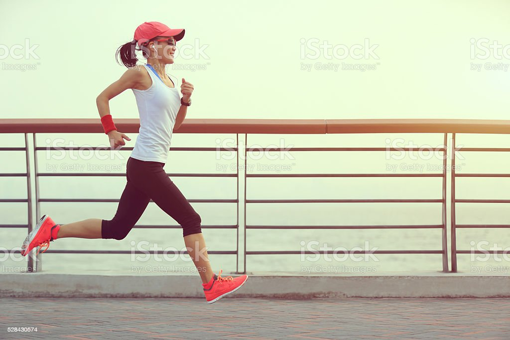 young fitness woman runner running at sunrise seaside stock photo