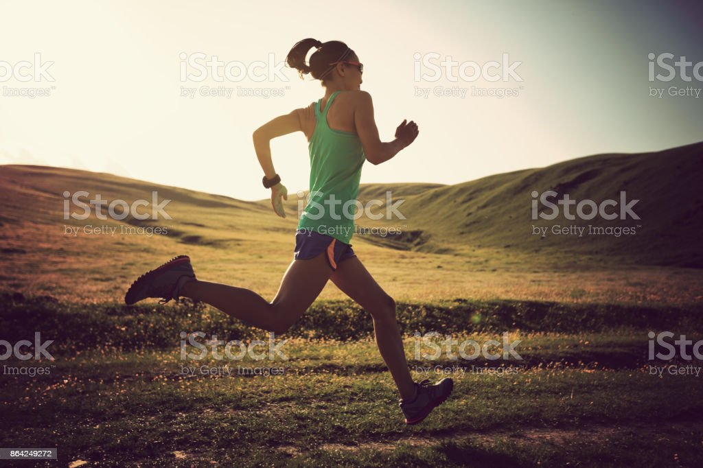 young fitness woman runner running on grassland trail royalty-free stock photo